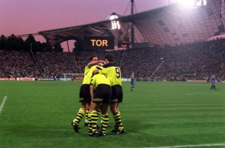 Football. UEFA Champions League Final. Munich, Germany. 28th May 1997. Borussia Dortmund 3 v Juventus 1. Borussia Dortmund's Karlheinz Riedle is congratulated by his team-mates after scoring his side's second goal, as the scoreboard in the background disp